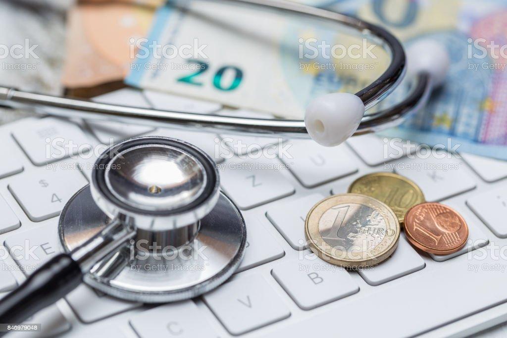 Stethoskop und Tastatur mit Münzen und Geld-Konzept – Foto