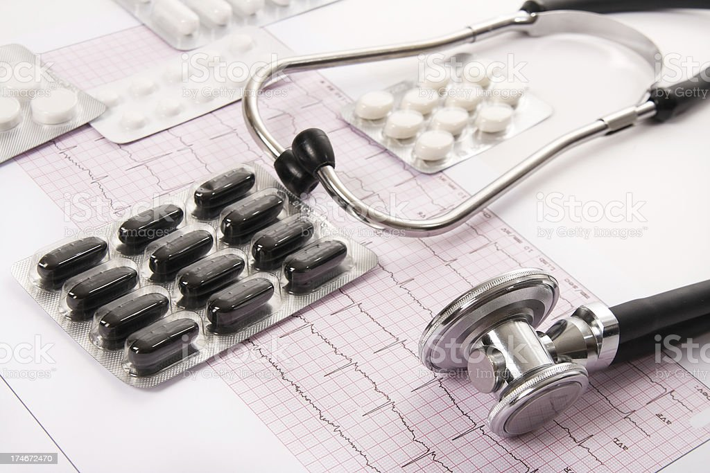 Stethoscope and pills on an EKG sheet.Close-up royalty-free stock photo