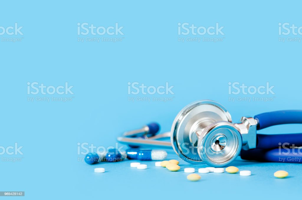 Stethoscope and pills on blue background royalty-free stock photo