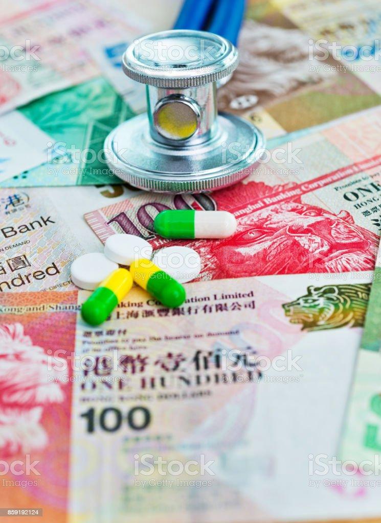 Stethoscope and pills on Hong Kong currency stock photo