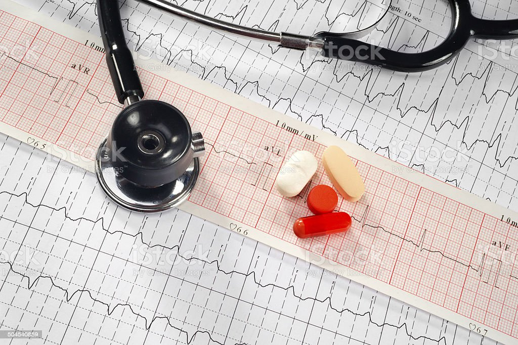 Stethoscope and pills on the cardiogram background stock photo
