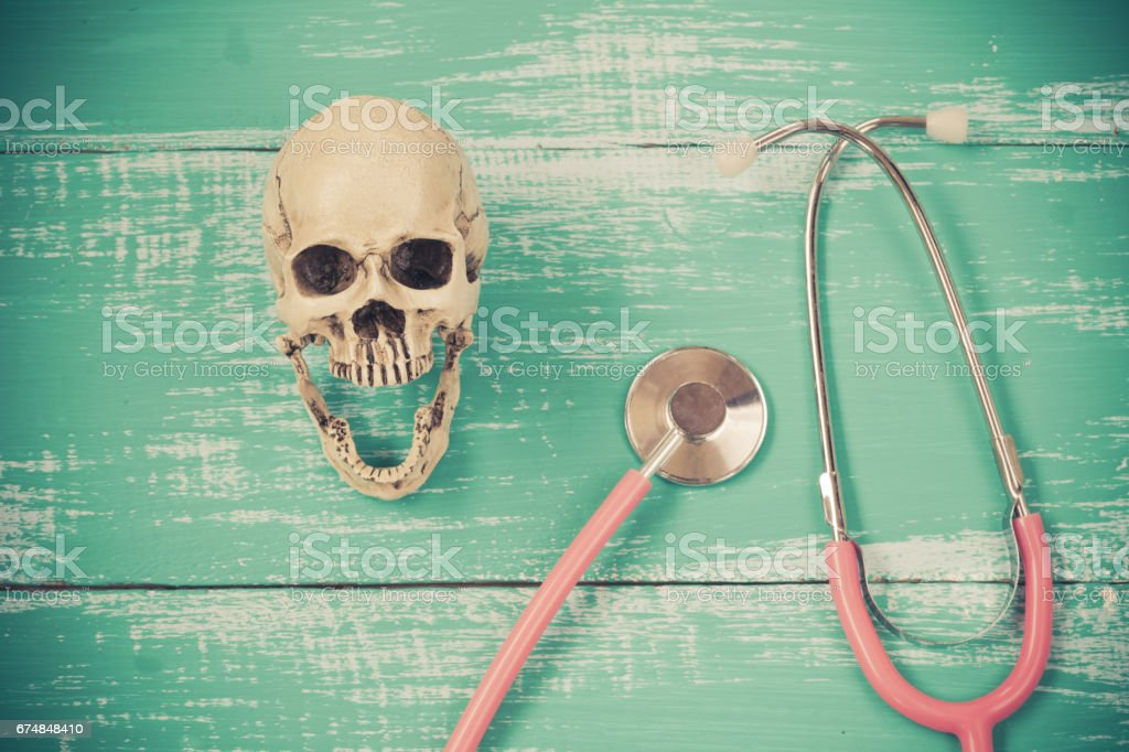stethoscope and skull on old wood background stock photo