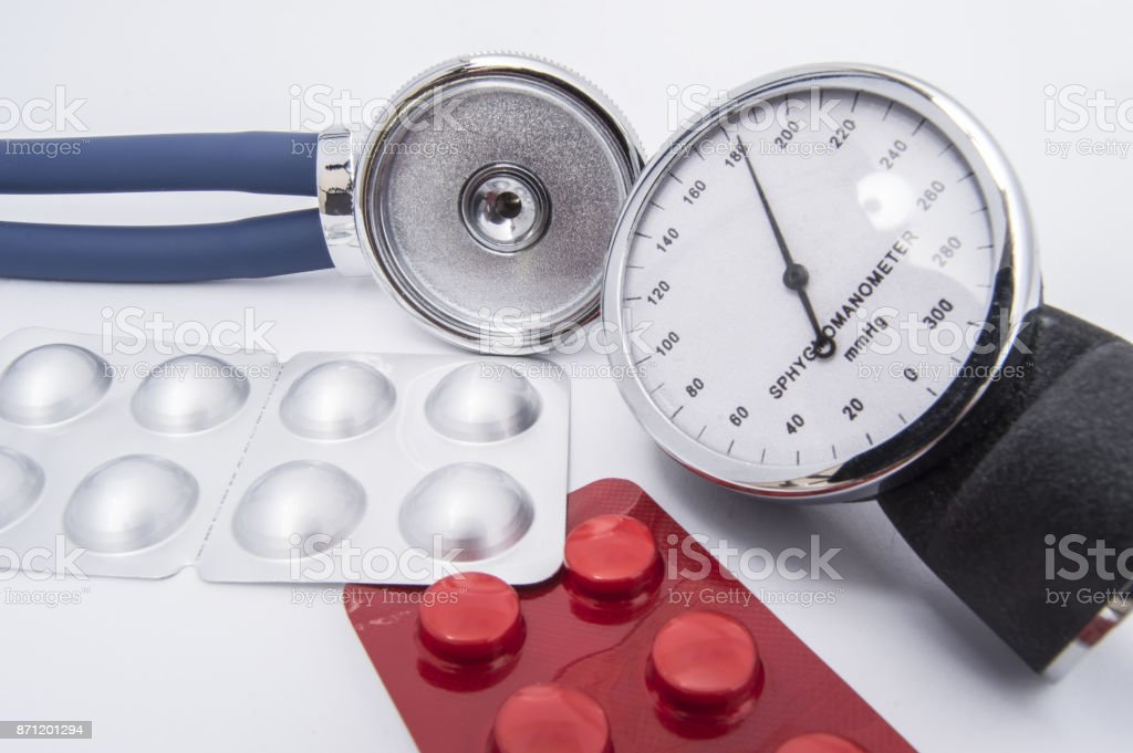 Stethoscope and sphygmomanometer dial with high indicators of arterial blood pressure lie on the white medical table near the pills and medicines in a red and chrome blister pack stock photo