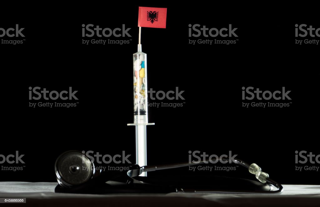 Stethoscope and syringe filled with drugs injecting the Albanian flag stock photo