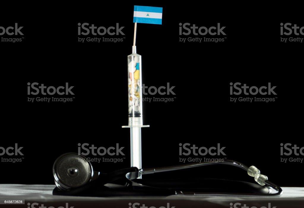 Estetoscopio y una jeringa llenan de drogas inyectables de la bandera de Nicaragua - foto de stock