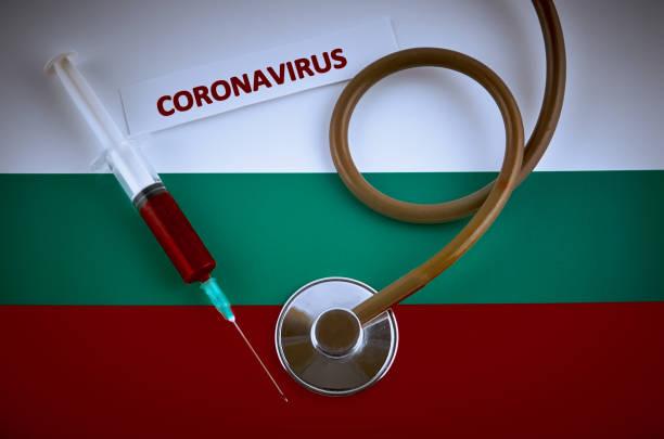 stethoscoop en spuit op de vlag van bulgarije met coronavirusetiket - bulgarije stockfoto's en -beelden