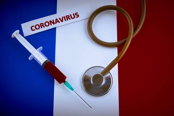 stéthoscope et seringue sur le drapeau de france avec l'étiquette de coronavirus - covid france photos et images de collection