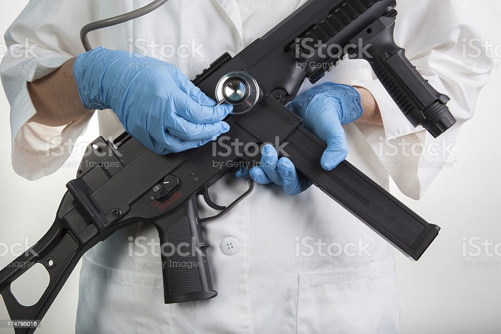 A scientist or a doctor holding a Stethoscope to an assault rifle....
