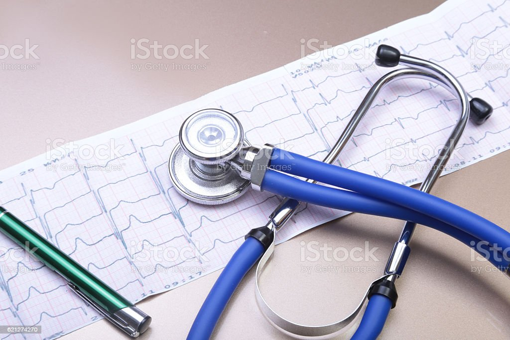 Stethoscope head and silver pen lying on cardiogram  clipboard stock photo
