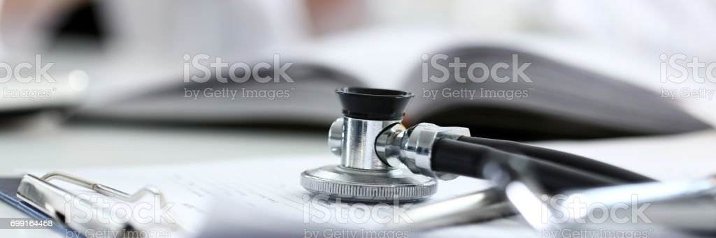 Stethoscope head lying on medical forms closeup while medicine doctor...