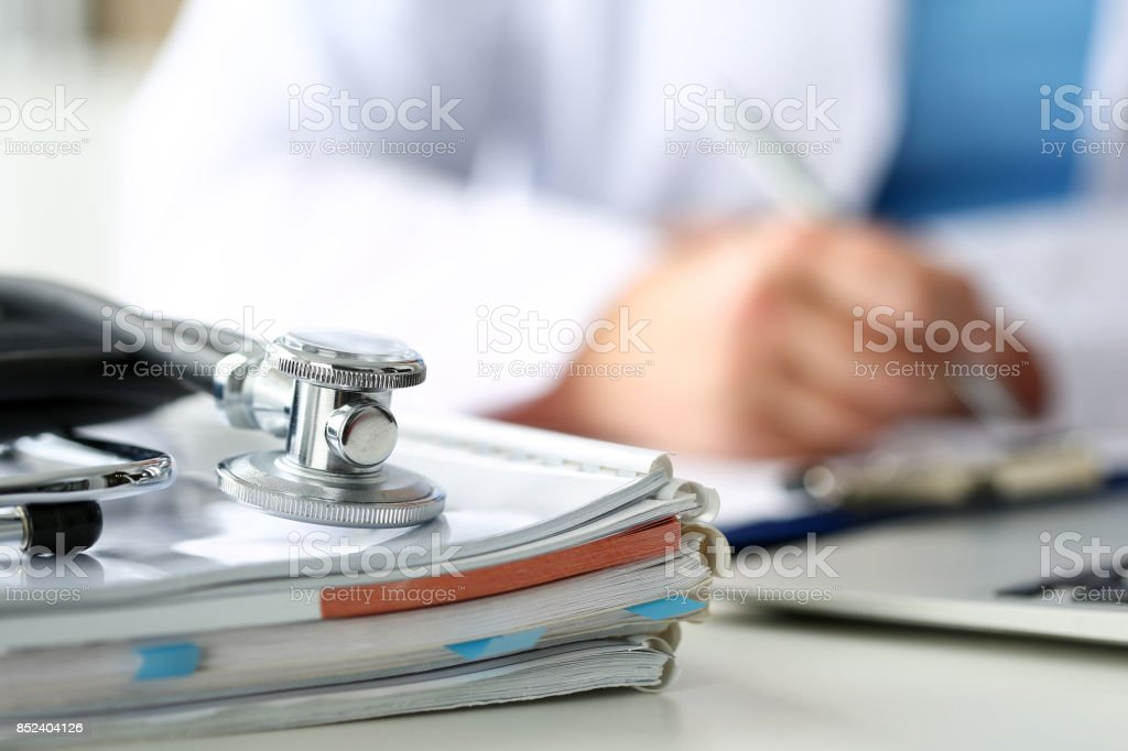 Stethoscope head lying on medical forms closeup stock photo