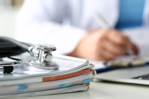 stethoscope head lying on medical forms closeup - doctors office stock pictures, royalty-free photos & images