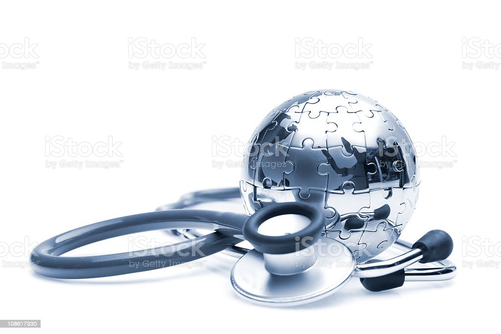 Stethoscope laying next to silver ball made of puzzle pieces stock photo