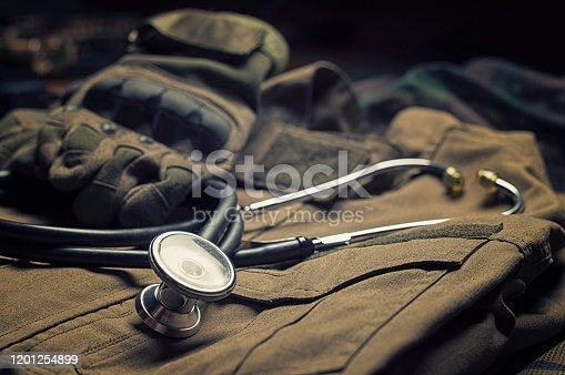 Stethoscope lies on the uniform of a US soldier. The concept of health care, military insurance, state care. Top view. Mixed media