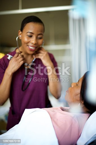 Young female African doctor listening with a stethoscope on a senior female patient in a hospital bed Cape Town South Africa