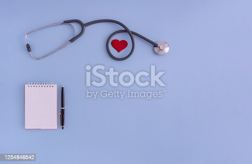 istock stethoscope, Notepad, pen, heart on a blue background. the concept of medicine, health control 1254846542