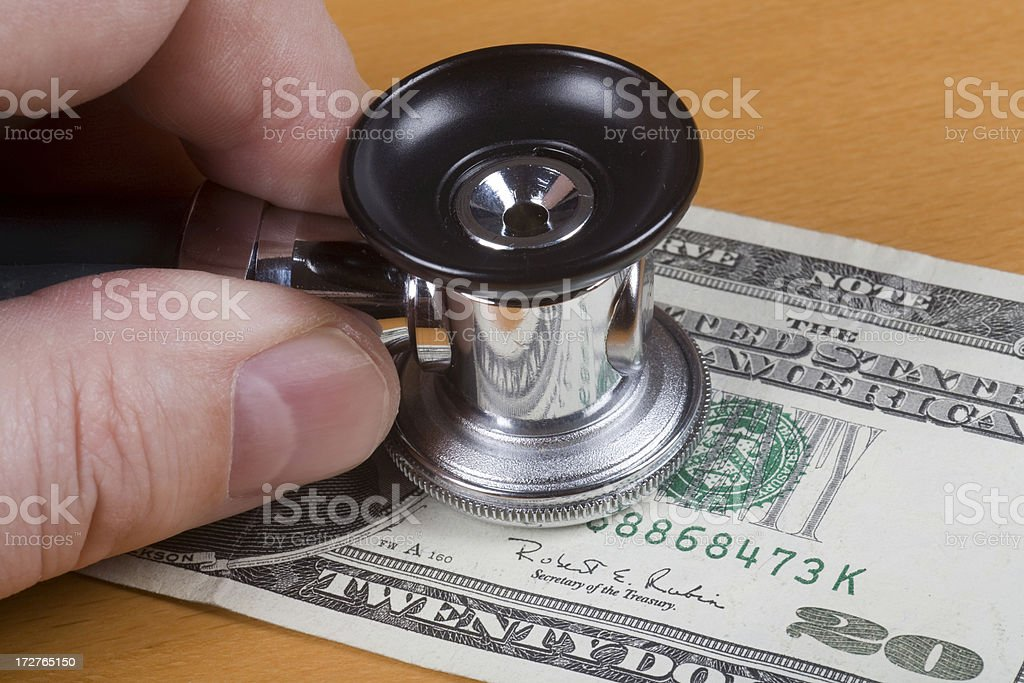 Stethoscope on a dollar bill stock photo