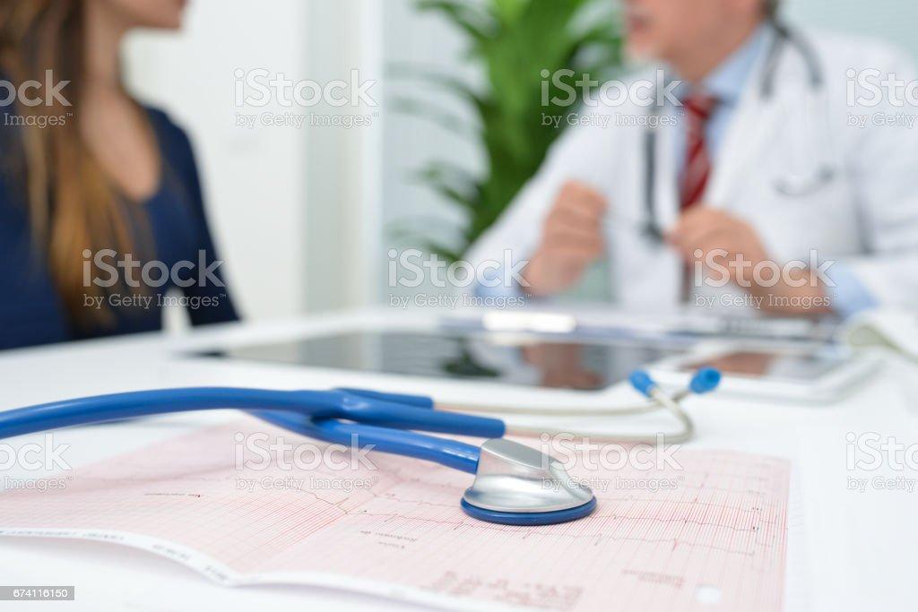 聽診器心電圖、 醫生和病人在背景中 免版稅 stock photo