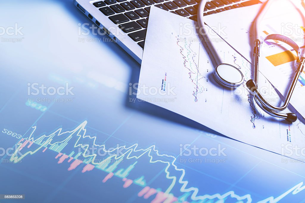 Stethoscope on computer keyboard Stethoscope on laptop keyboard with financial report Analyzing Stock Photo