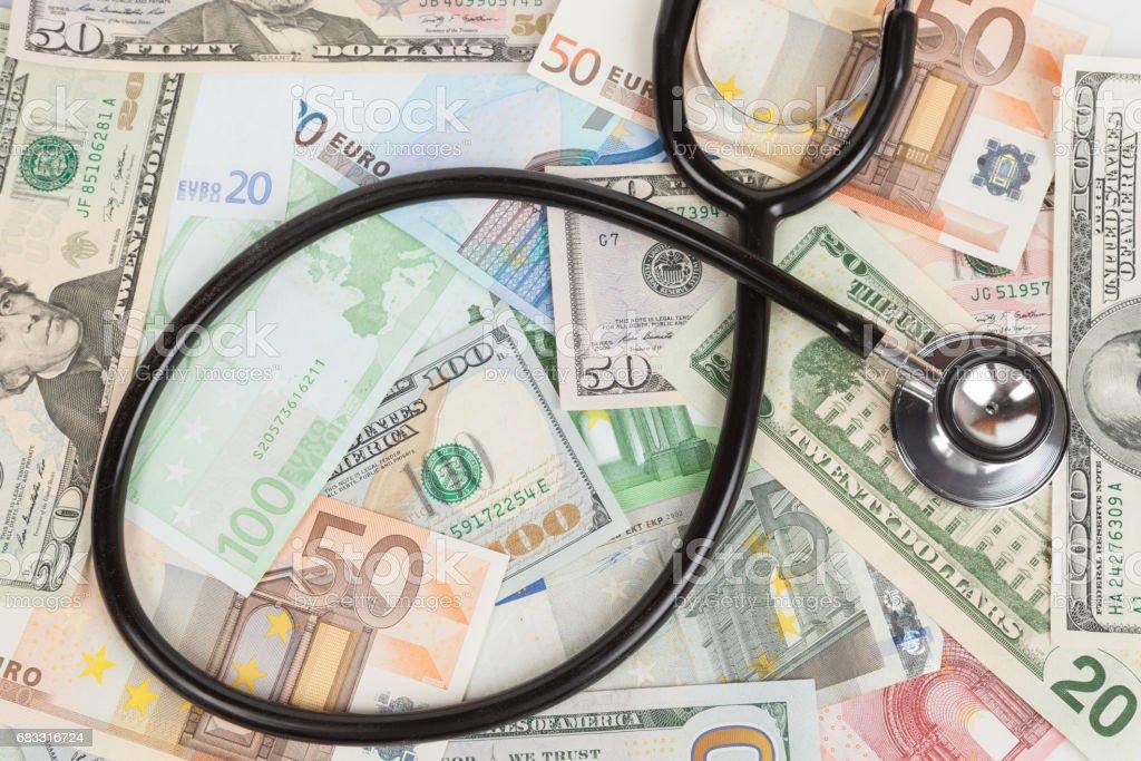 Stetoskop på euron och US-dollar sedel royaltyfri bildbanksbilder