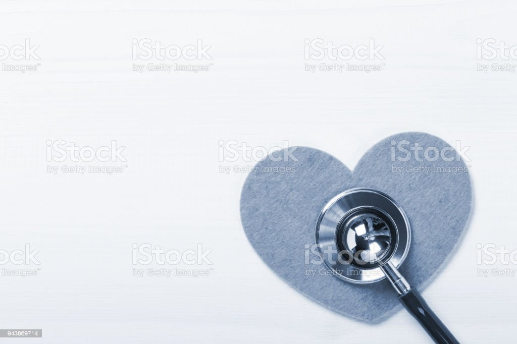 Stethoscope on heart shape over white wooden background stock photo