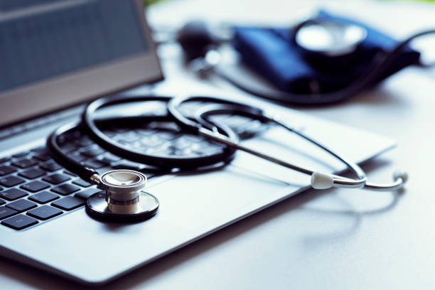 Stethoscope on laptop keyboard in doctor surgery Stethoscope on laptop keyboard in doctor surgery with blood pressure monitor general practitioner stock pictures, royalty-free photos & images