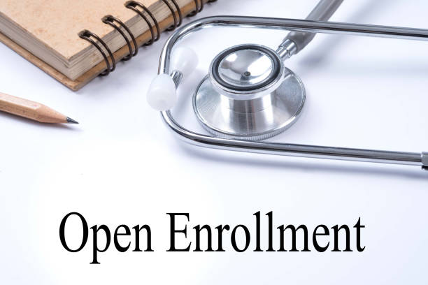 stethoscope on notebook and pencil with open enrollment words as medical concept. - open enrollment stock photos and pictures