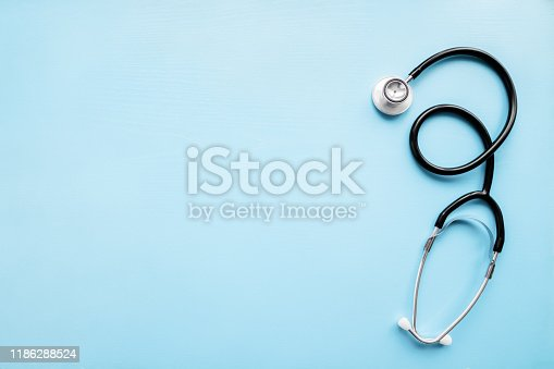 Stethoscope on pastel blue table. Doctor tool. Healthcare concept. Empty place for text. Flat lay. Closeup. Top down view.