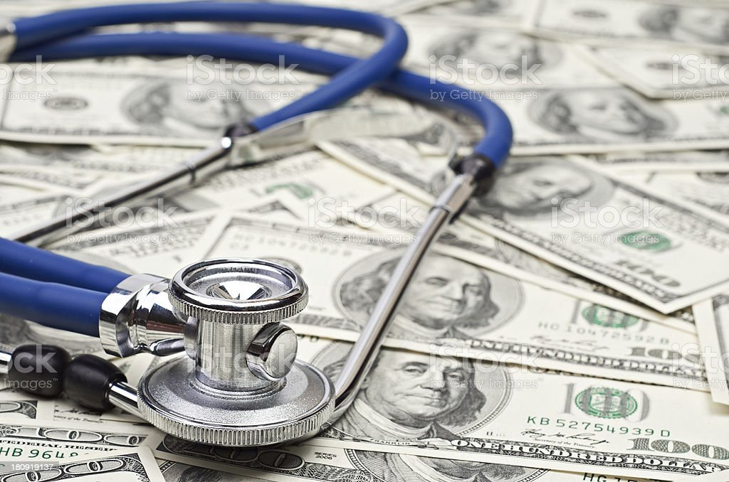 Stethoscope on pile of hundred dollar bills stock photo