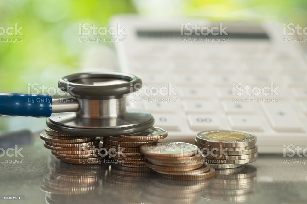Stethoscope on stack of coins with calculator, concept of Financial Health stock photo