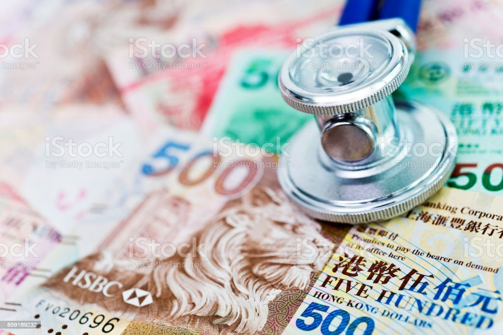 Stethoscope on top of Hong Kong dollars stock photo