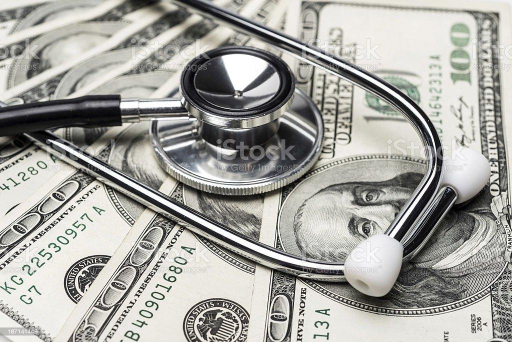 stethoscope on top of hundred dollar bills stock photo