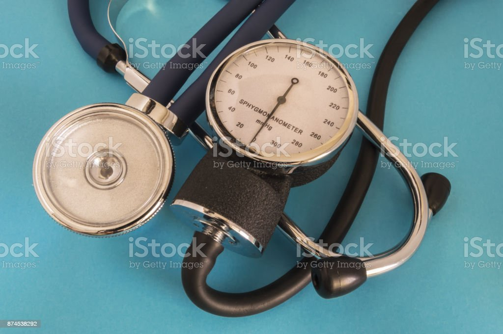 Stethoscope or phonendoscope and manual aneroid sphygmomanometer dial lay crosswise on a blue background in the doctor's office stock photo