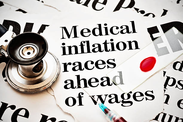 Stethoscope, syringe, blood smear on headlines about medical cost inflation stock photo