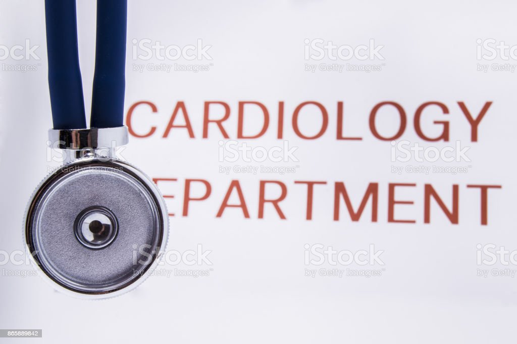 A stethoscope with blue flexible tubing hanging on the background of the inscription Cardiology Department and the entrance to this department in the hospital stock photo