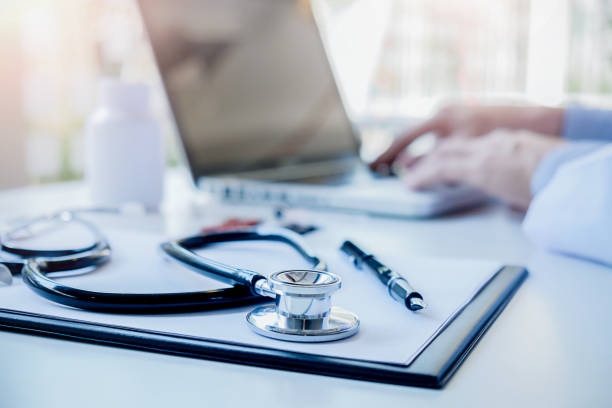 Stethoscope with clipboard and Laptop on desk Doctor working in hospital writing a prescription  Healthcare and medical concept test results in background vintage color selective focus. stock photo