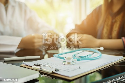 istock Stethoscope with clipboard and Laptop on desk,Doctor working in hospital writing a prescription, Healthcare and medical concept,test results in background,vintage color,selective focus 1131513138