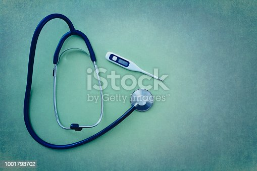 Stethoscope with digital thermometer on green background