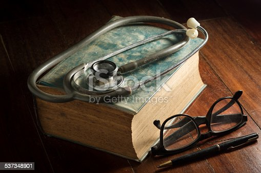 istock Stethoscope with eyeglasses,pen and antique book. 537348901