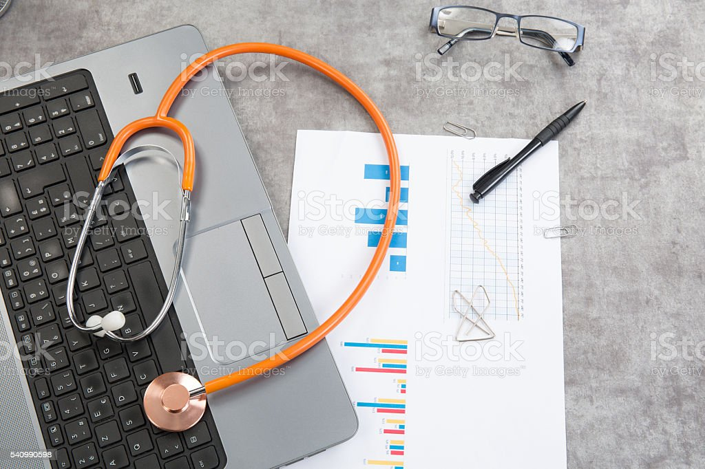 Stethoscope with financial on the desk and a laptop stock photo