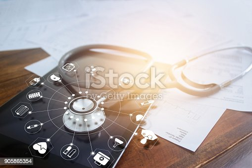 istock Stethoscope with icon medical on tablet and wooden table background 905865354