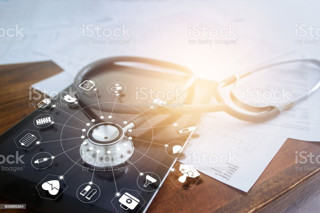 Stethoscope with icon medical on tablet and wooden table background stock photo