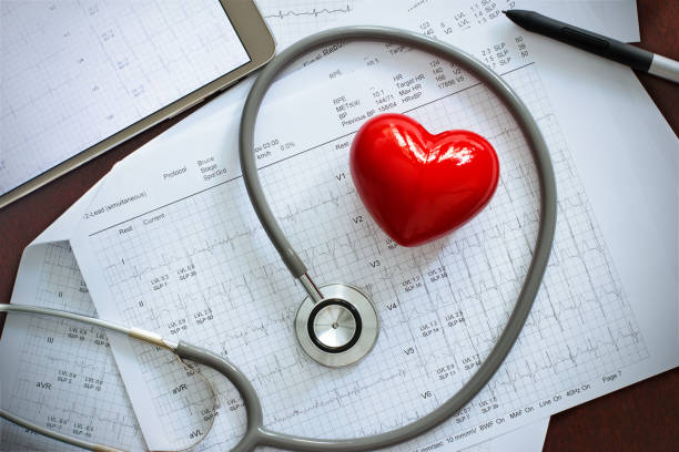 Stethoscope with red heart shape and annual heart health exam report, medical health care concept stock photo