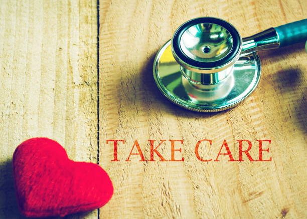 stethoskop mit kümmern sich um wort und rot herzform auf holztisch - herz zitate stock-fotos und bilder