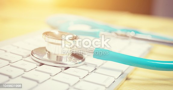 istock Stethoscope,a medical instrument for listening to action of heart or breathing lay on laptop keyboard in hospital,relax time doctor,selective focus,vintage color.morning light 1049601998