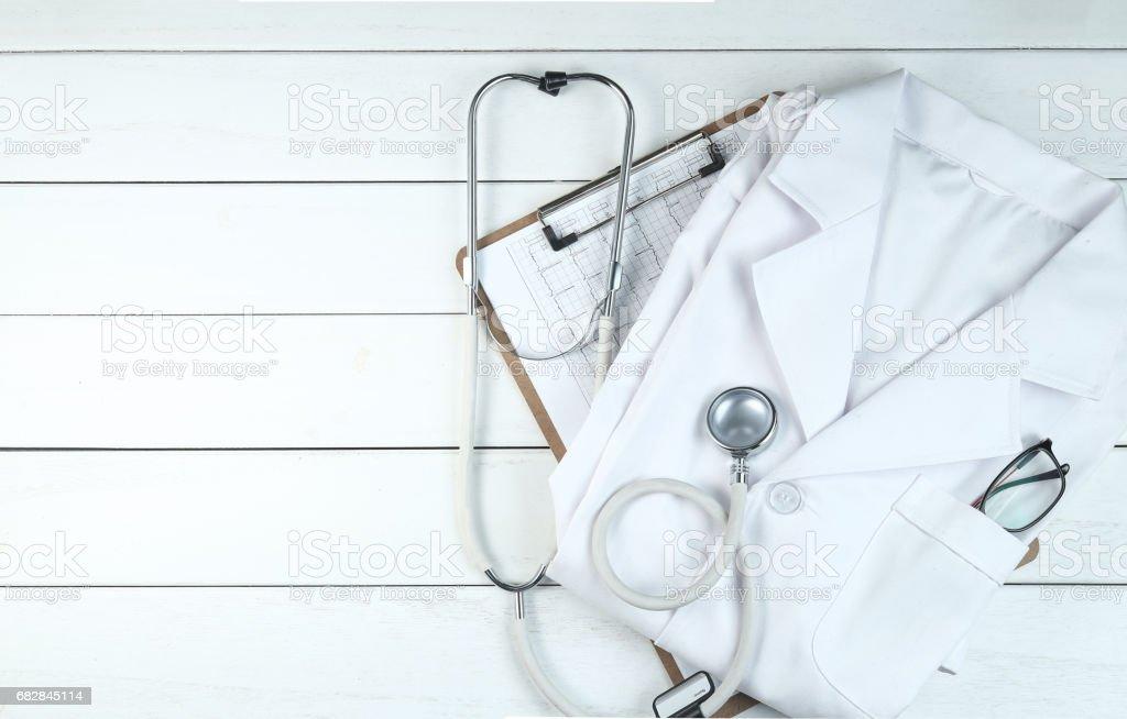 stethoscope,clipboard and doctor's uniform on white neat wooden desk Lizenzfreies stock-foto