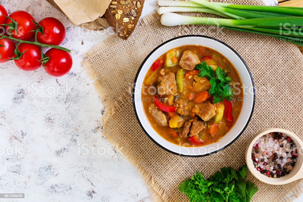 Stew with meat and vegetables in tomato sauce on white background. Top view stock photo