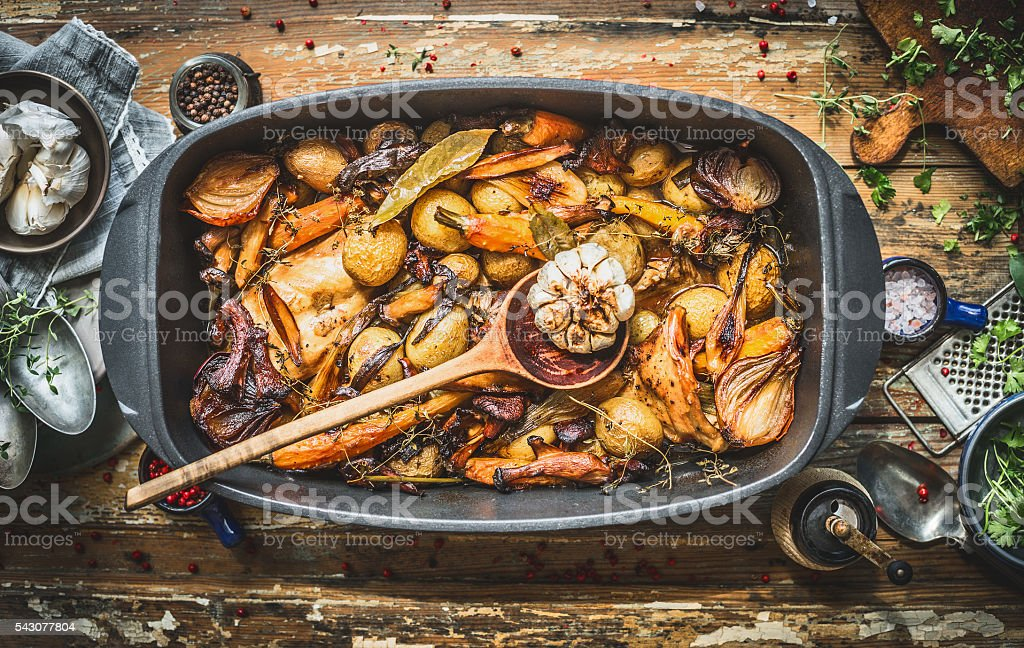 Stew with roasted vegetables, forest mushrooms in cooking pot stock photo
