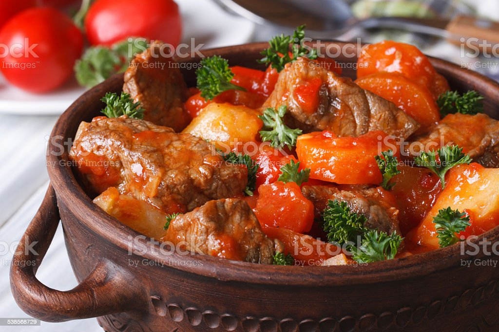 stew with tomato sauce and vegetables closeup in a pot stock photo