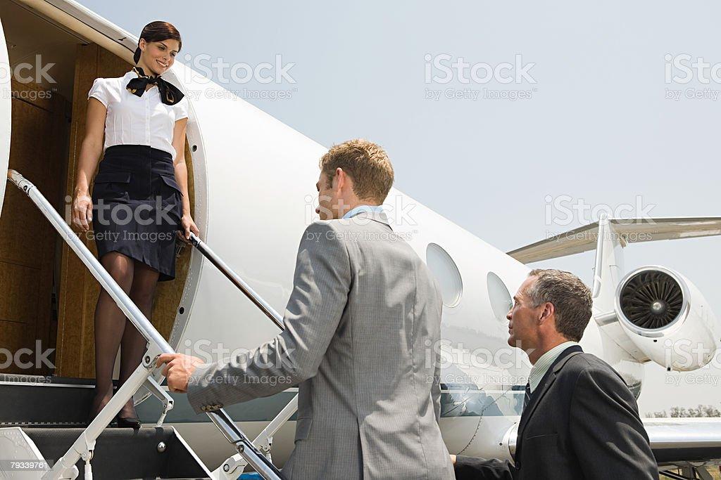 Stewardess and businessmen boarding jet stock photo
